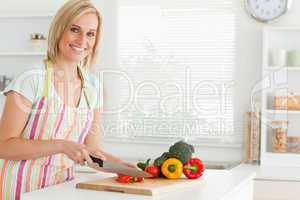 Cute woman cutting red pepper looks into camera