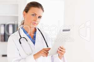 Charming doctor having a stethoscope around her neck pointing at