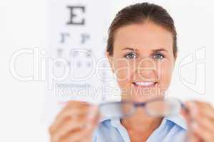 Portrait of a brunette eye specialist handing out glasses lookin