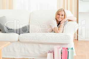 Woman lying on her couch after shopping