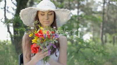Young woman with bouquet resting on nature in forest