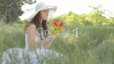 Young woman with bouquet of wild flowers on nature