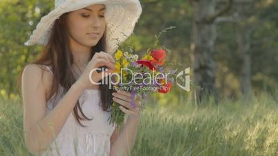 Young woman smelling bouquet of wild flowers on nature