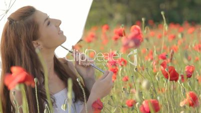 Young woman with white umbrella sitting on chair among poppies