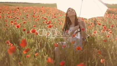 Young woman twisting white umbrella, sitting on chair among poppies