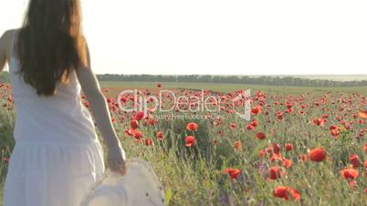 Young woman in white sundress walking through red poppies field