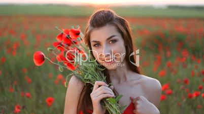 Young woman with bouquet of red poppies on meadow