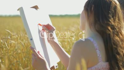 Young woman with boy drawing with crayons in the field