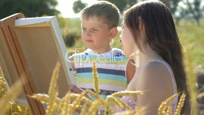 Young woman with little boy drawing together on paper canvas