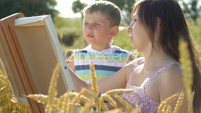 Young woman helping little boy in painting on the field