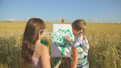 Woman with little boy engaged in green finger painting outdoors
