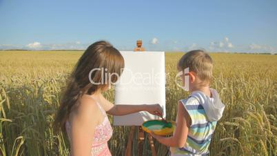 Woman with little boy drawing with fingers in the field