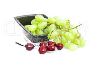 cherries with drops of water in a spoon and a bowl of grapes iso