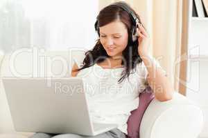 Dark-haired woman relaxing on a sofa with headphones and a noteb