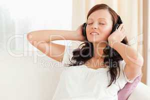 Dark-haired woman relaxing on a sofa with headphones