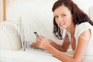 Dark-haired woman doing some online shopping looking into the ca