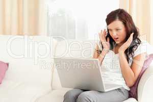 Amazed woman sitting on a sofa with a laptop