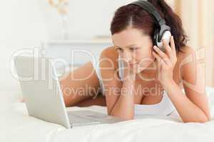 Woman listening to music working on a laptop