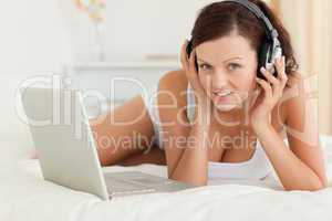 Woman listening to music working on a laptop looking at the came