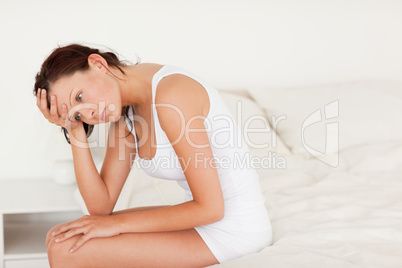 Sad woman sitting on her bed