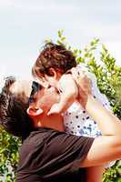 father in early thirties gives his son a kiss on the cheek in th