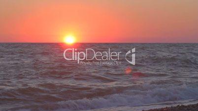 Sun hanging low over imaginary horizon of the sea edge
