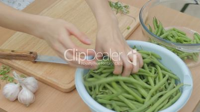 CLIP EDIT  Trimming fresh green beans on wooden chopping board outdoors