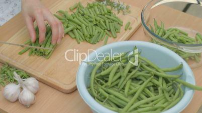 CLIP EDIT  Slicing fresh green string beans on wooden chopping block