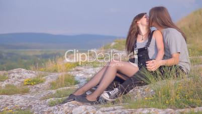 CLIP EDIT Young couple sitting on the slope, kissing looking away outdoors
