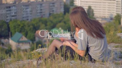 CLIP EDIT Happy young couple sitting on slope gently touching each other