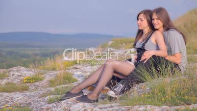 CLIP EDIT Nice young woman and man sitting in grass on hill