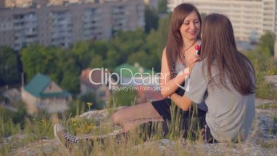 CLIP EDIT Young romantic couple sitting on slope, sharing lollipop, smiling, kissing