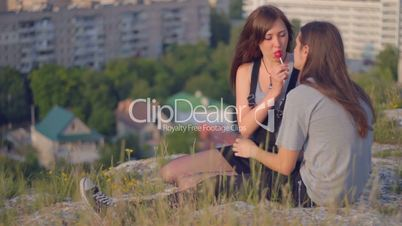 CLIP EDIT Happy young couple in love licking lollipop on slope outdoors