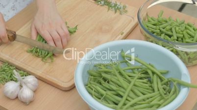 Bunch of French green beans being cut with sharp knife