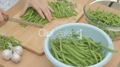 Slicing fresh green string beans in equal parts on board