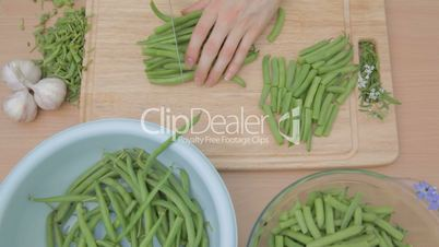 French green beans being cut with sharp knife outdoors