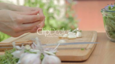 Clearing away dry husk of the garlic cloves outdoors