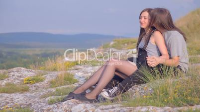 CLIP EDIT Romantic young couple sitting on slope gently touching each other