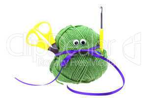skein of wool with eyes, ribbon, scissors and crochet hooks isol
