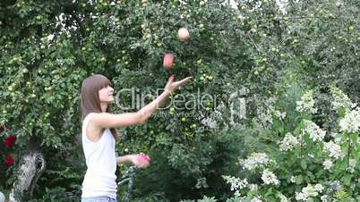 Pretty girl juggling with three apples