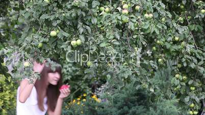 Pretty girl eating red apple in the garden