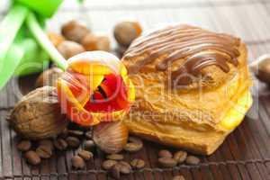 cake with chocolate, coffee bean, tulip and nuts lying on a bamb