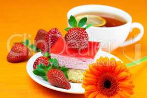 gerbera, lemon tea, cake and strawberries lying on the orange fa
