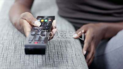 Woman holding remote control and watching tv
