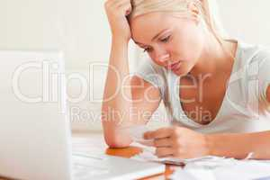 Stressed blond woman doing paperwork