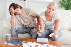 Worried couple calculating expenses