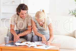 Smiling couple calculating their expenses