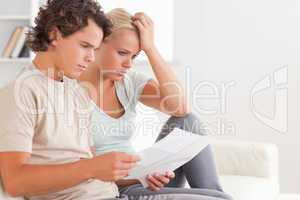 Despaired couple reading letters
