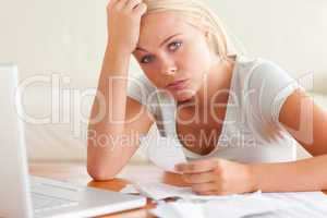 Worried woman doing accounts looking into the camera