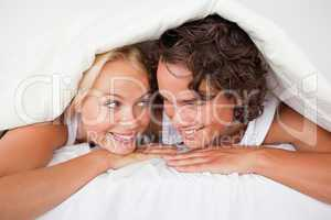 Couple under a duvet with a knowing smile